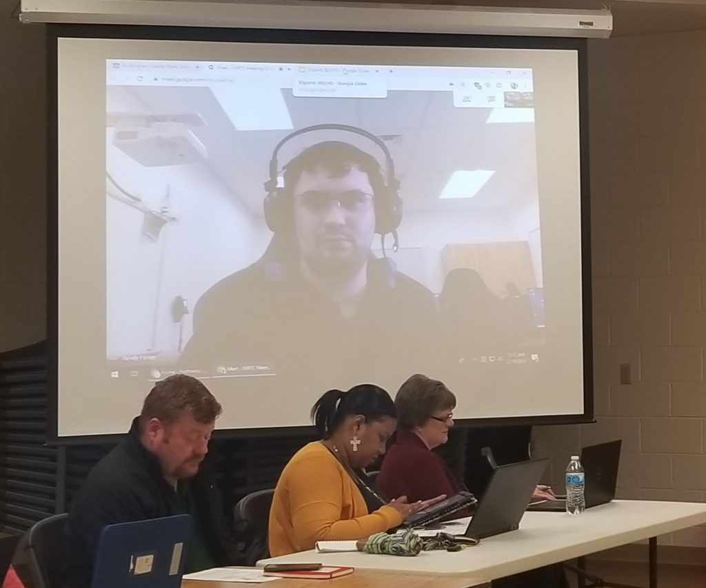 Man on screen with headphones.